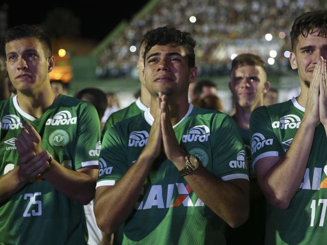 Chapecoense soccer players who did not travel with their team on a flight to Colombia that crashed, mourn during a tribute to the crash victims. Picture: AP/Andre Penner