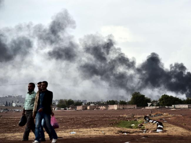 Displaced ... Kurdish men walk close to the Turkish-Syrian border as smoke rises from the town of Kobane. Pic: AFP PHOTO / ARIS MESSINIS