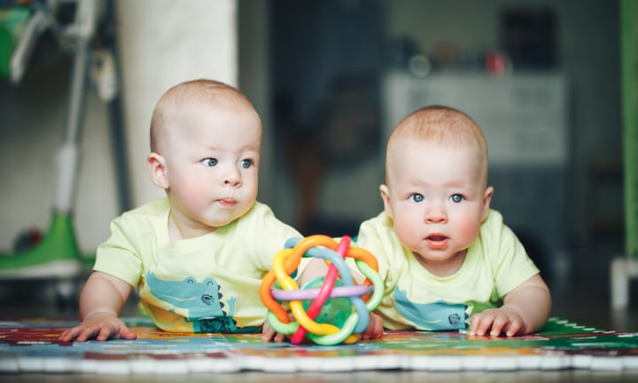 Little Baby Child Twins Brothers Six Months Old is Playing on the Floor