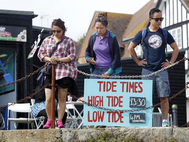 Racing the clock ... a sign indicates tide times as people search a beach in Folkestone, southeast England, for gold bullion buried there by German artist Michael Sailstorfer. Picture: Jack Taylor