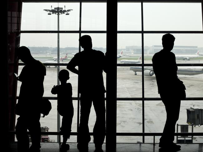Passengers look through a window while airliners line up at Beijing International Airport. Picture: AP