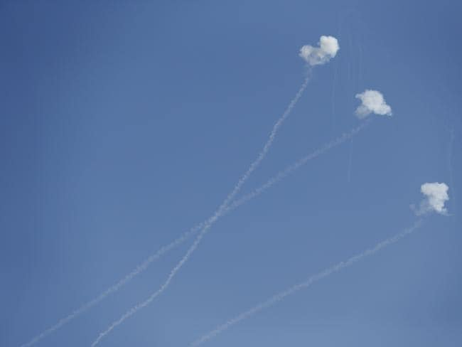 Three Iron Dome rockets ... explode after being launched from the Gaza strip by Palestinians militants, as seen from the Israel Gaza border, southern Israel. Picture: Lefteris Pitarakis