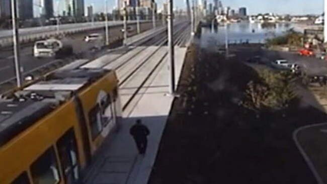 A man trespasses on light rail tracks near the tram bridge at Southport, walking alongside a passing tram and up the bridge.