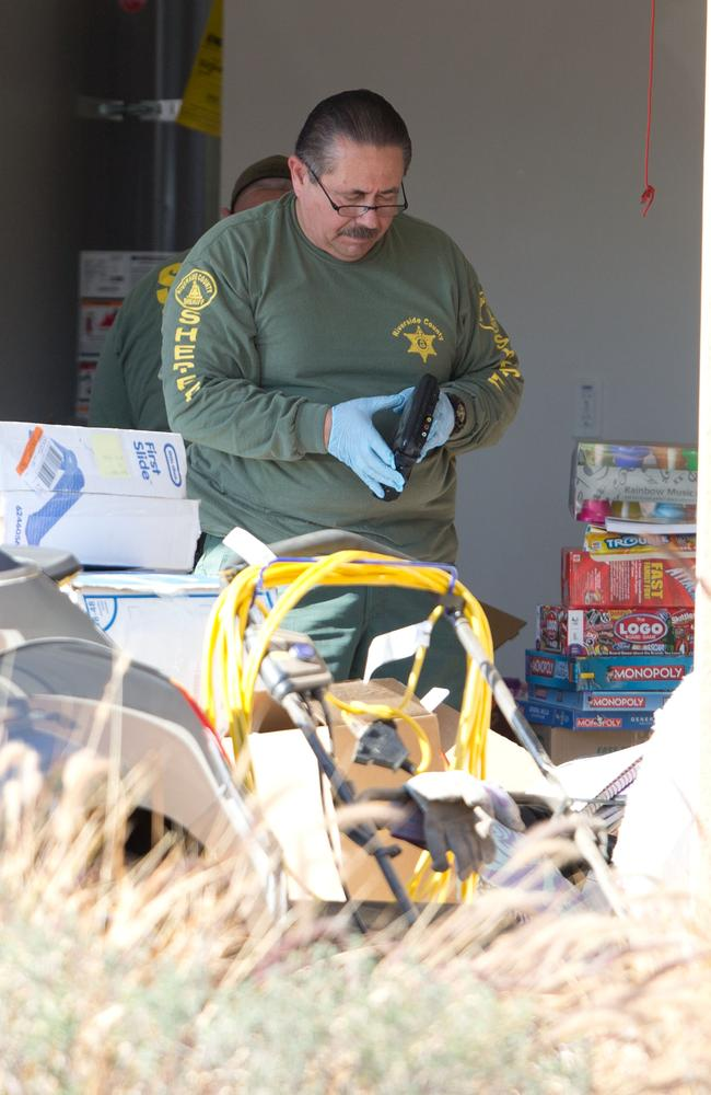 Police teams search the garage on 18 January, 2018. Board games and a baby's first slide box can be seen. Picture: Mega