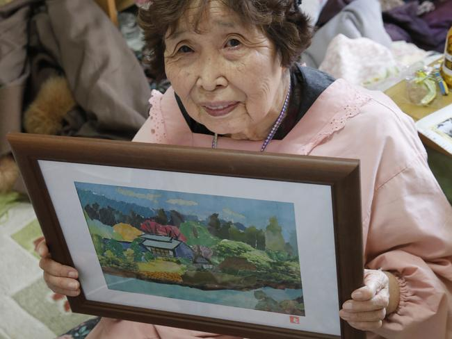 Tokiko Onoda, 80, who fled her home near the tsunami-crippled power plant, shows a painting of her hometown of Namie at her cramped, cluttered apartment where she lives with her husband. Picture: AP