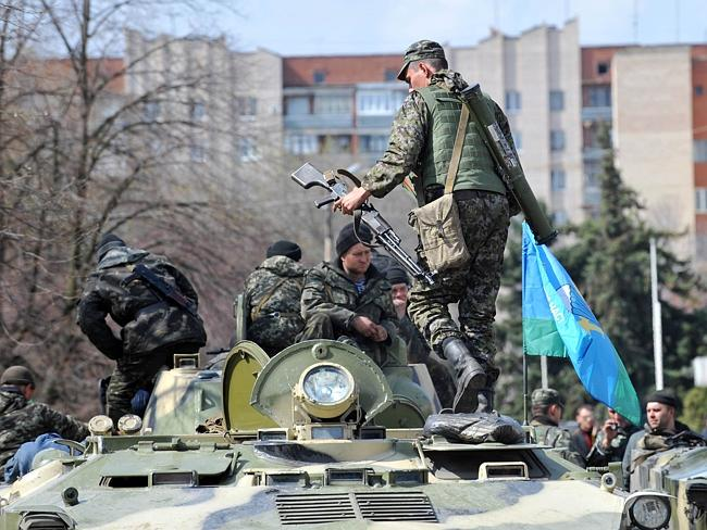 Ready to fight ... armed men wearing military fatigues stand guard by Armoured Personnel Carriers (APC) outside the regional state building seized by pro-Russian separatists. Picture: Genya Savilov