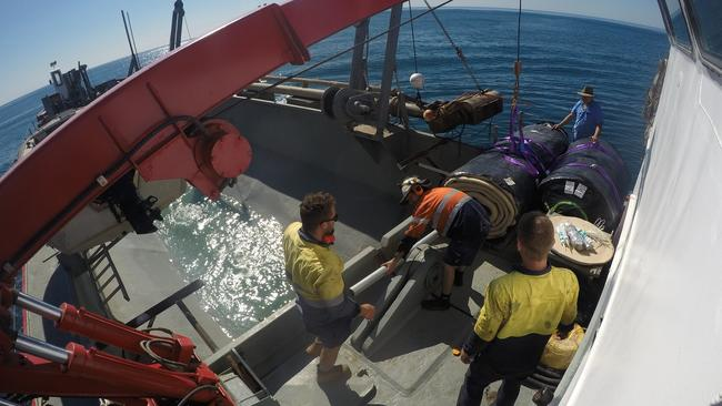 Workers on the boat before dropping the sandbag on the reef. Photo: Gold Coast Bulletin