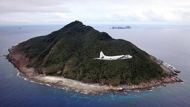 A P-3C patrol plane of Japanese Maritime Self-Defense Force flying over the disputed islets known as the Senkaku islands in J...
