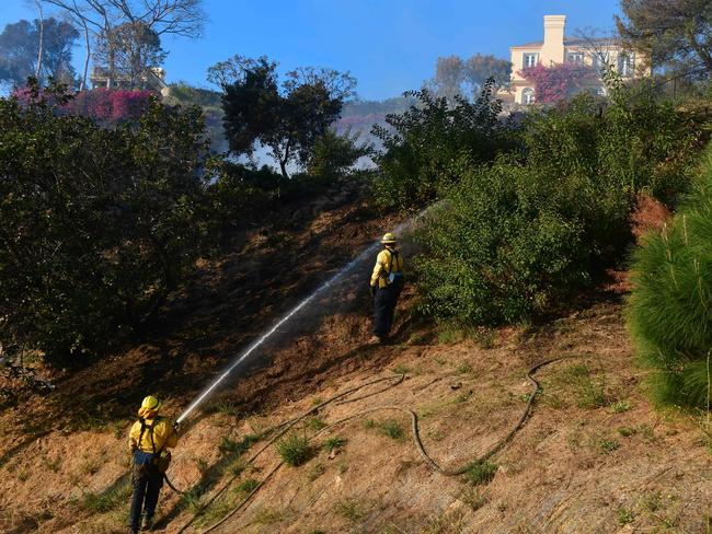 Firefighters put out burning embers on a hillside beneath homes in the exclusive suburb of Bel Air. Picture: AFP/Frederic J Brown
