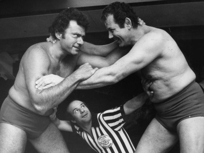 Referee Tony Mareno is dwarfed by wrestlers Spiros Arion and Mario Milano.
