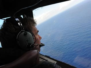 (FILES) This file photo taken from a Royal New Zealand Airforce (RNZAF) P-3K2-Orion aircraft on April 13, 2014 shows co-pilot and Squadron Leader Brett McKenzie helping to look for objects during the search for missing Malaysia Airlines flight MH370, off Perth. The official search for MH370 may have been called off but experts believe the missing airliner will one day be found, perhaps either by deep-sea miners or treasure hunters lured by a huge cash reward. After spending almost three years and 150 million USD on a deep sea hunt for the Malaysian passenger jet in the remote Indian Ocean off western Australia, top aviation investigators have been forced to admit they have come up with nothing. / AFP PHOTO / POOL / GREG WOOD / TO GO WITH Australia-Malaysia-China-MH370-aviation,FOCUS by Glenda KWEK