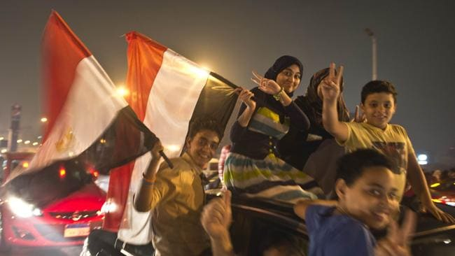 An Egyptian family celebrates in Cairo after a broadcast confirming that the army will temporarily be taking over from the country's first democratically elected president Mohammed Morsi. Picture: Khaled Desouki