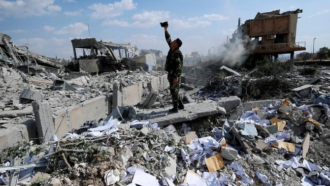A Syrian soldier films the damage of the Syrian Scientific Research Center which was attacked by US, British and French military strikes in retaliation to President Bashar Assad's suspected chemical attack against civilians, in Barzeh, near Damascus, Syria. Picture: AP /Hassan Ammar.