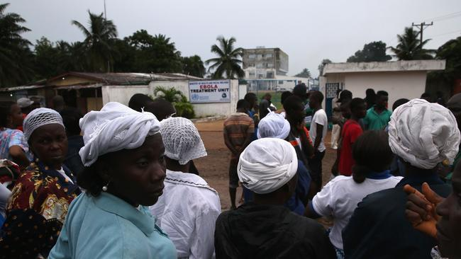Fear factor ... people gather outside the Island Clinic Ebola treatment centre in Monrovia. A planned strike was averted as most nurses and health care workers reported for work. Picture: Getty