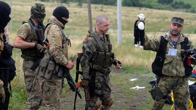 A pro-Russia militant holds up a stuffed animal as others look on at the site of the crash. Pro-Russian separatists and officials in Kiev blamed each other for the crash. Picture: AFP