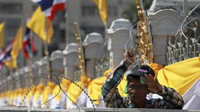 A protester removes barbed wires outside the Government House in Bangkok, Thailand, as demonstrators swarmed the Thai prime minister's office compound after three days of bitter clashes. Picture: Wason Wanichakorn