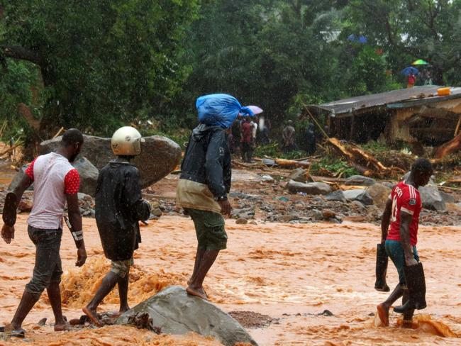 Residents walk through floodwaters past a damaged building in an area of Freetown. Picture: AFP