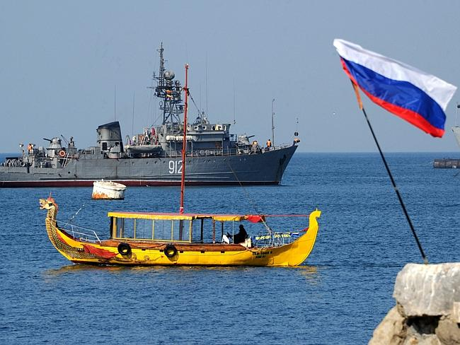 Crimea... A Russian flag floats in the wind as a Russian Navy ship remains stationed in the harbour of Sevastopol, Crimea. Picture: Viktor Drachev/AFP