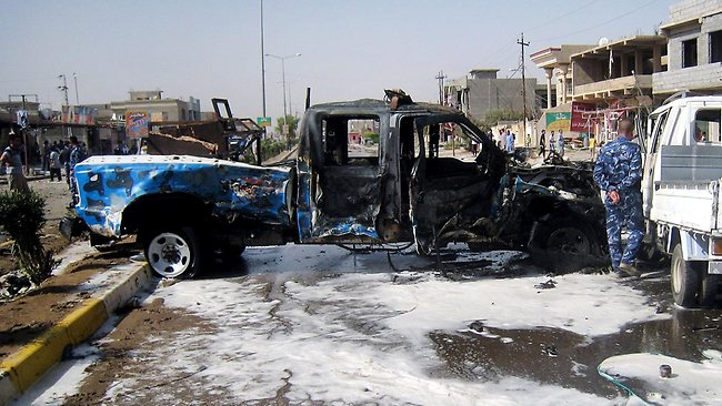A police officer inspects a police vehicle destroyed by a car bomb attack in Kirkuk, 290km north of Baghdad.