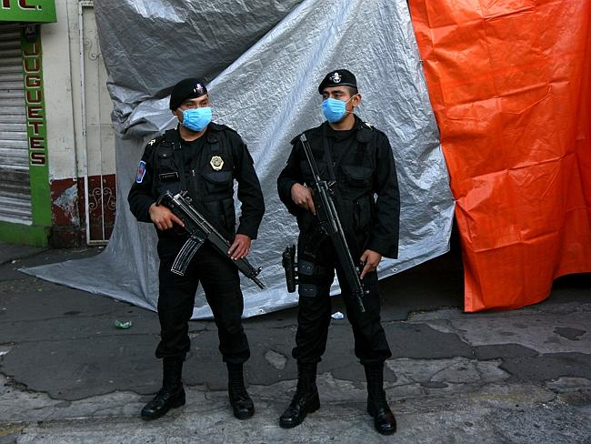 Mexico City police guard a refrigerated truck carrying bodies that were found in mass graves in northern Mexico.