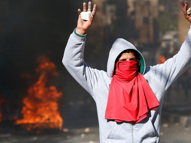 A Palestinian protester holds up stones during clashes with Israeli security forces in the city centre of the West Bank town of Hebron. Picture: AFP.