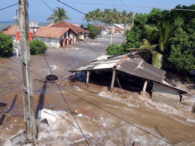 Tidal waves wash through houses at Maddampegama, about 60 kilometres south of Colombo, Sri Lanka. Picture: AP / Gemunu Amarasinghe