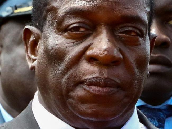 (FILES) This file photo taken on January 7, 2017 shows Zimbabwe acting President Emmerson Mnangagwa (C) attending the funeral ceremony of Peter Chanetsa at the National Heroes Acre in Harare.  Robert Mugabe has been removed as president of Zimbabwe's ruling ZANU-PF party and replaced by his former vice president Emmerson Mnangagwa, a party delegate told AFP on November 19, 2017 outside a meeting in Harare. / AFP PHOTO / Jekesai NJIKIZANA
