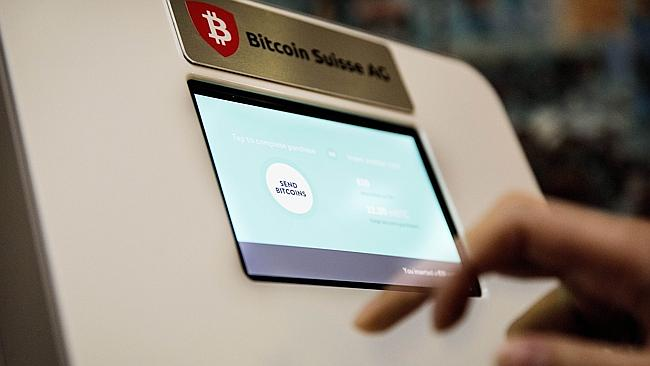 A person uses a bitcoin ATM machine in a restaurant in The Hague. AFP/VALERIE KUYPERS