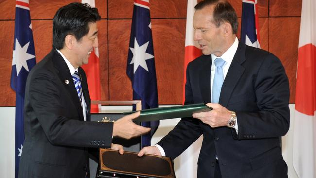 Done deal ... Japanese Prime Minister Shinzo Abe and Australian Prime Minister Tony Abbott exchange documents after signing the Japan-Australia Economic Agreement and the Agreement on the Transfer of Defence Equipment and Technology at Parliament House. Picture: Mark Graham
