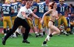 <p>A security guard chases a topless female streaker running across the field during the final match of the American Football Austrian Bowl in Schwechat</p>