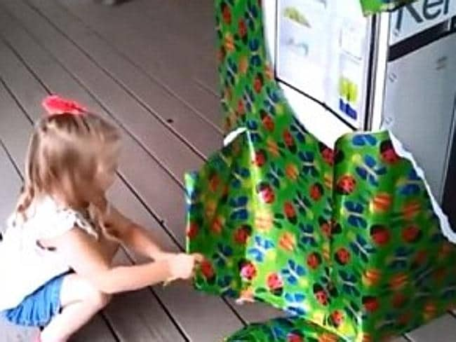Bit by bit, she removes all the wrapping paper.