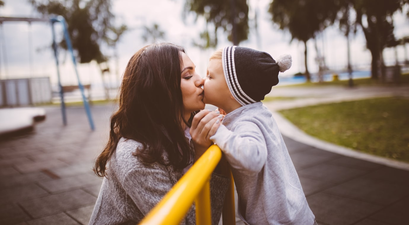 Son giving a kiss to his mother at the playground