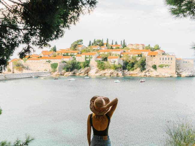 Woman standing on the background of Sveti Stefan island, Montenegro