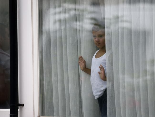A young boy ... looks out of a window on a street in Edmonton, north London. Picture: AFP