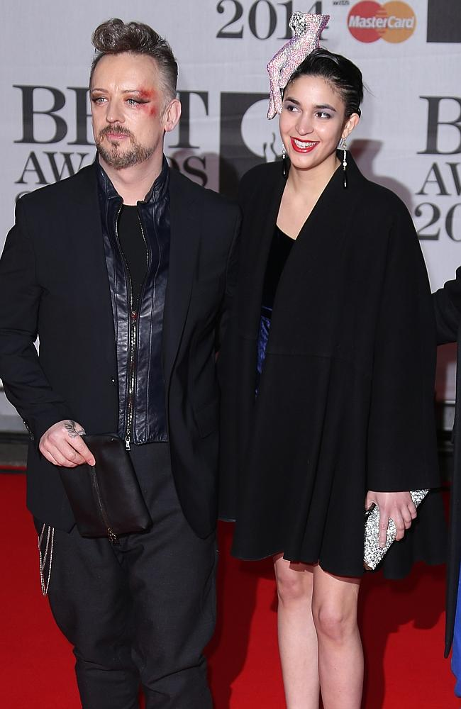 From left, British singer-songwriter Boy George, and an unknown guest.