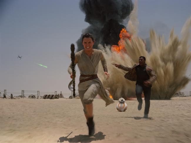 Daisy Ridley and John Boyega with droid BB-8 in a scene from film Star Wars: The Force Awakens.
