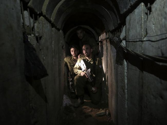 Israeli soldiers walk through a tunnel discovered near the Israel Gaza border in October 2013. Picture: Tsafrir Abayov