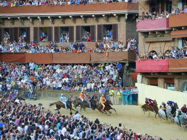 Riders compete during the Palio horse race in Siena on July 2, 2013. The Palio medieval race is held twice a year in Siena with jockeys riding bareback around a makeshift race course set up in the city's central square. AFP PHOTO/ FABIO MUZZI RESTRICTED TO EDITORIAL USE - NO MARKETING NO ADVERTISING CAMPAIGNS