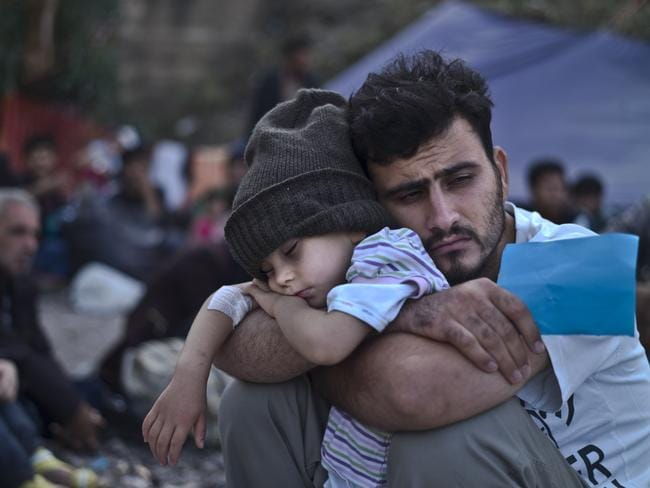 A Syrian refugee child sleeps on his father's arms while waiting at a resting point to board a bus in Greece. One of the lucky children who escaped Syria. Picture: AP/Muhammed Muheisen