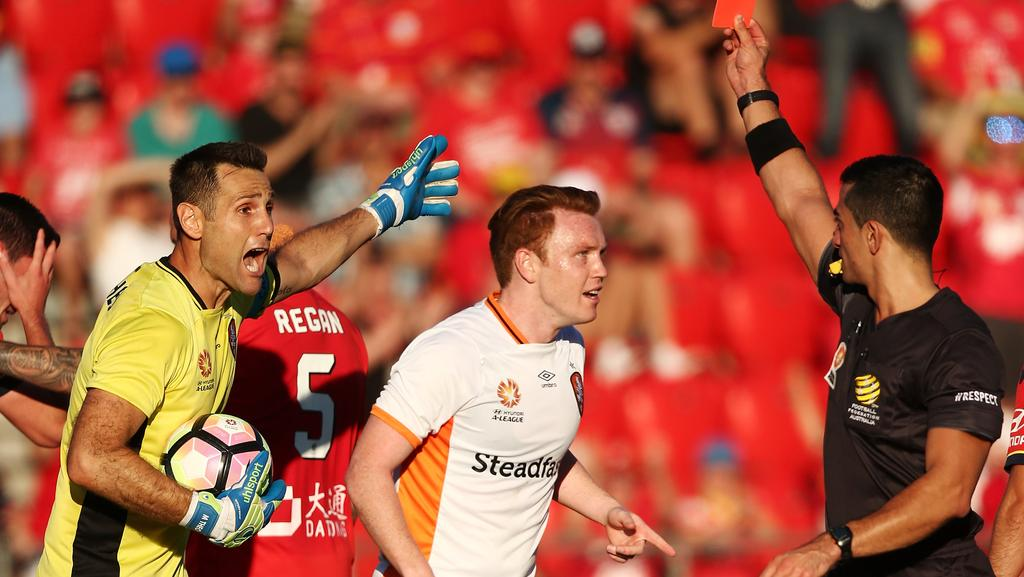 Michael Theo of Brisbane Roar is shown a red card by referee Stephen Lucas.