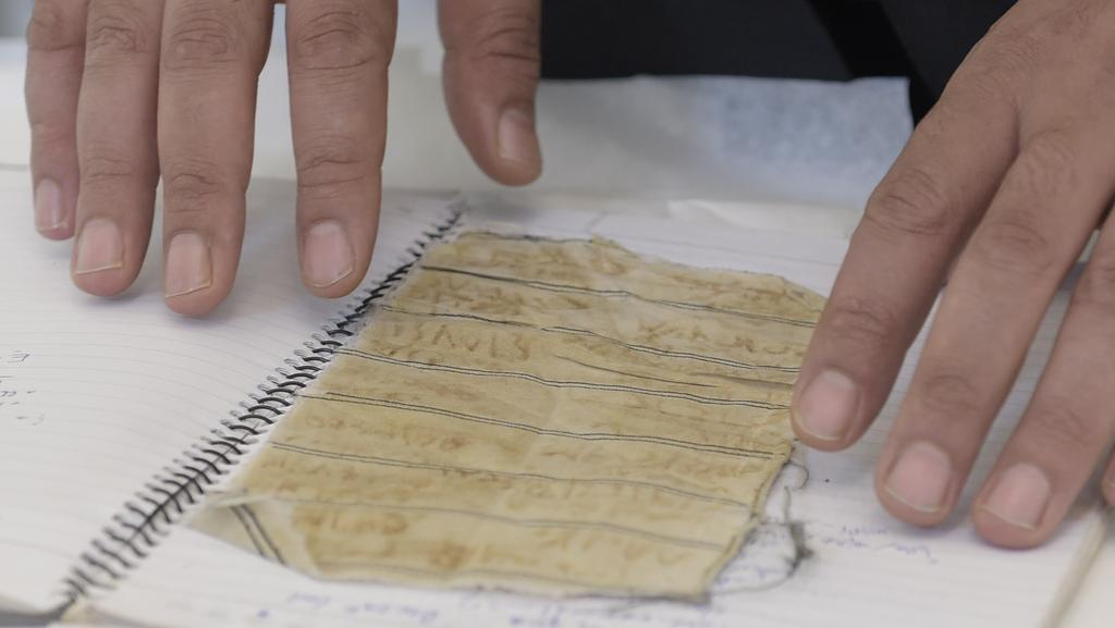 Mansour Omari, a Syrian human-rights activist documenting cases of people who have disappeared under President Bashar Assad's government, shows scraps of fabric with the names of fellow inmates for the US Holocaust Memorial Museum for preservation. Picture: AP/Susan Walsh