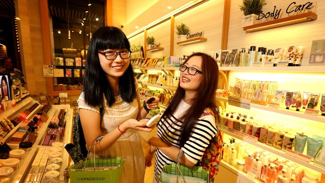 Chinese tourists Amanda Wang and Ling Li enjoy some of Melbourne's shopping. Picture: Stuart McEvoy