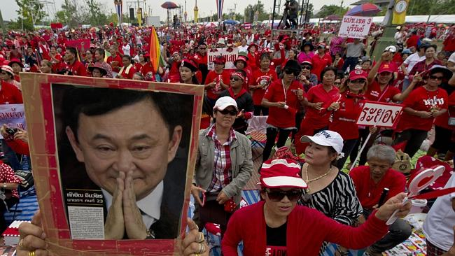 "Supporters ... ""Red Shirt"" protesters hold a portrait of fugitive former premier Thaksin Shinawatra during a rally on Saturday. Picture: AFP"
