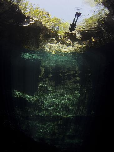 A woman free diving in a blue hole in the Bahamas.