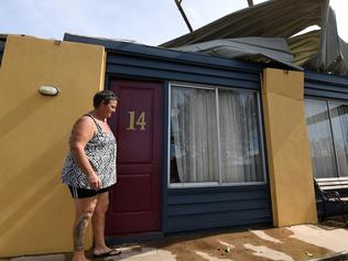 Kerry Campbell inspects damage to her motel in Proserpine, Thursday, March 30, 2017. Cyclone Debbie hit Queensland's north coast on Tuesday as a category 4 cyclone, causing wide spread damage. (AAP Image/Dan Peled) NO ARCHIVING