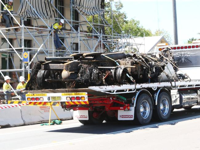 The burnt-out truck body is transported past the scene of yesterday's destruction in Singleton. Picture: Peter Lorimer