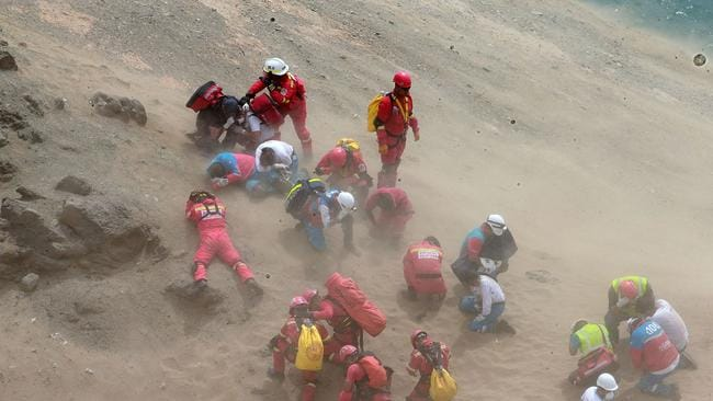 Rescuers and firefighters covering themselves from sand being blown by the wind during rescue efforts. Picture: AFP