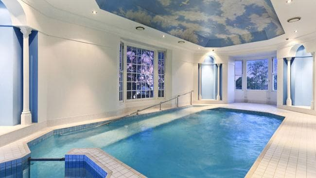 The room with the inground pool and spa is complete with downlights, columns, large windows and ceiling wallpaper.