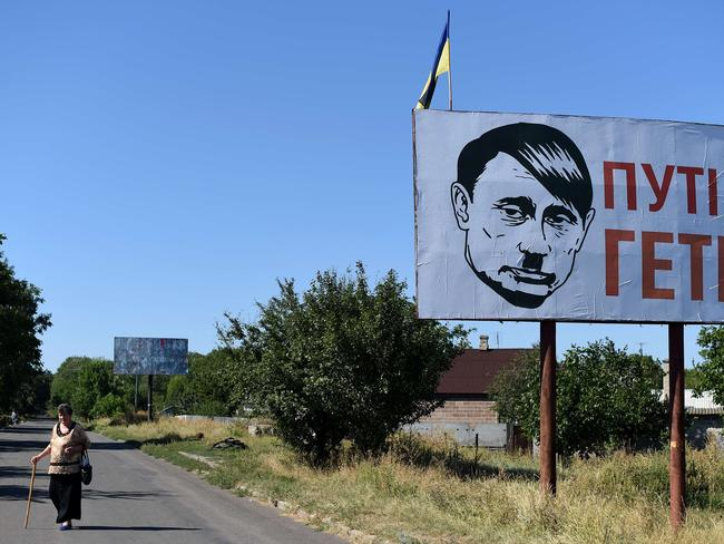 Advance halted ... A villager walks past an Ukrainian flat and a bilboard and despicting Russian president Vladimir Putin bearing a Hitler moustache and haircut. The mysterious new offensive follows significant gains by Ukrainian forces. Source: AFP