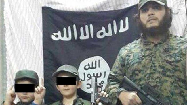 Khaled Sharrouf, whose Australian citizenship was revoked, with boys believed to be his sons in front of the Islamic State flag in an image posted on Twitter. Source: Supplied